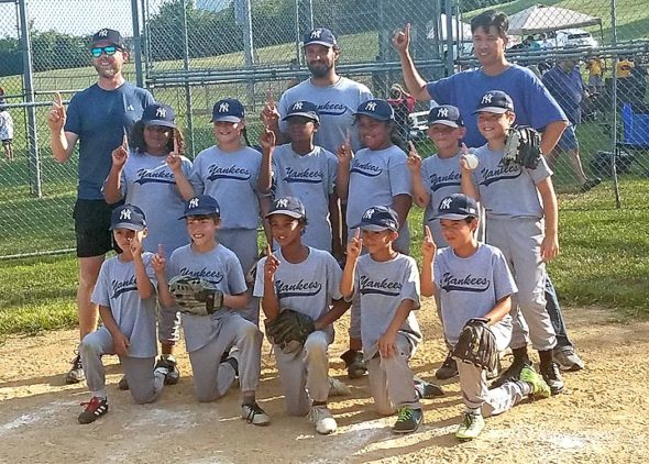 The Nipper's Corner Yankees were this year's Yellow Springs Youth Baseball Minor League champions, winning Saturday's championship game 19–8 over the Sam and Eddie's Open Books Brewers. From left, top row, are Head Coach Patrick Lake and assistant coaches Mark Breza and Derek Barker; middle row: Emery Fodal, Noelle Fisher, Sameer Sajabi, Ella Fodal, Henry Lake and Aiden Gustafson; bottom row: Marco Meyer, Nierin Barker, Nico Sajabi, Zander Breza and Kyu Flateau. Not pictured: Assistant Coach Brian Machi, Vincent Machi and David Scott Jr. (Photo by Jeanna GunderKline)