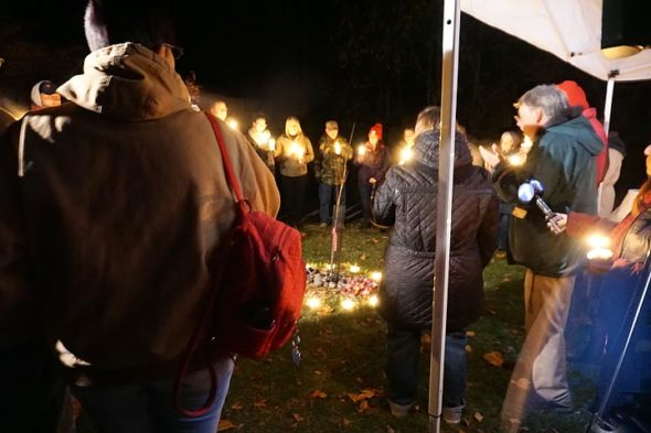"""About 40 people gathered Saturday evening, Nov. 16, to remember Leonid """"Lonya"""" Clark on his 27th birthday. Friends and family formed a candle-lit circle around a memorial tree planted in Clark's honor just south of the Women's Park on Corry Street. (Photo by Carol Simmons)"""