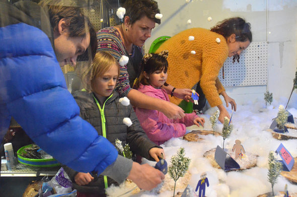 Pictured decorating the window at Yellow Springs Hardware are members and parents from Cub Scout Pack #578, from left, John Hempfling with son Rocket Cowperthwaite, Monica Bellant and daughter Harper Seybold, and Leslie Roeth, whose son Otono was nearby. Their winter theme included snow camping. (Photo by Matt Minde)
