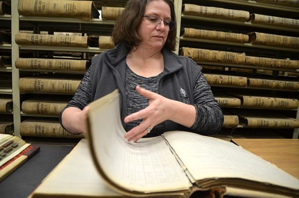 """Greene County Archivist Robin Heise flips through property records detailing all the plots of land owned by Yellow Springs founding father William Mills in the 19th century. (Photo by Lauren """"Chuck"""" Shows)"""