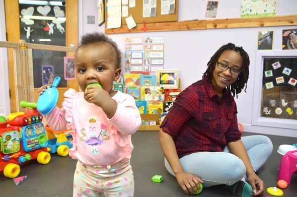 The Yellow Springs Community Children's Center now enrolls infants aged six weeks to 17 months. The infant program at the almost 75-year-old local nonprofit opened in November, with four infants so far, including Zsa'Lynn, 10 months, who loves to dance and chew. Looking on is lead teacher Aille Turner, an experienced infant and toddler caregiver. (Photo by Audrey Hackett)
