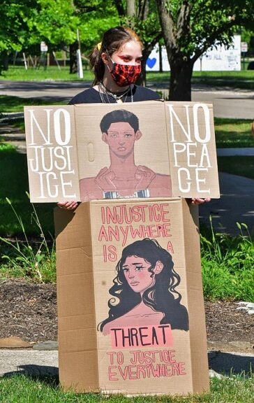 """""""Empowering Black Women"""" was the theme of the most recent anti-racism rally, held Saturday, July 11, near the Yellow Springs Public Library, and followed by a march. Here, artist Abby Flanagan stood by some of her original artwork. (Photo by Kathleen Galarza)"""