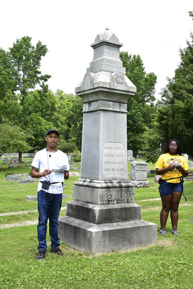 Youth tour guides Griffin Roberts and Gini Meekin shared information about Wheeling Gaunt and his wife Amanda, at their gravesite. (Photo by Kathleen Galarza)