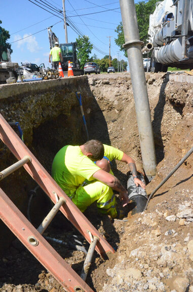 Village street crew members Dustin Harris and Austin Pence (partially obscured) repaired a broken water line under Dayton Street near Kenneth Hamilton Way on Monday, July 26. (Photo by Matt Minde)
